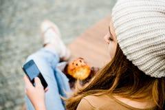 Jugendlicher, der das Muffin schaut im Telefon isst Stockbilder