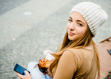 Jugendlicher, der das Muffin schaut im Telefon isst Stockbild