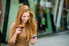 Jugendlicher, der das Muffin schaut im Telefon isst Lizenzfreie Stockfotografie