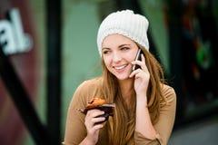 Jugendlicher, der das Muffin schaut im Telefon isst Lizenzfreies Stockbild
