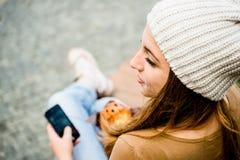 Jugendlicher, der das Muffin schaut im Telefon isst Stockfotografie