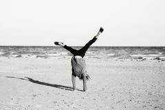 Jugendlicher, der das Wagenrad spielt auf Strand tut lizenzfreies stockbild