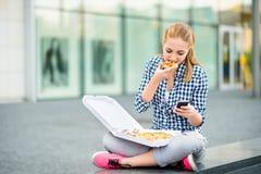 Jugendlicher, der die Pizza schaut im Telefon isst Stockfotografie
