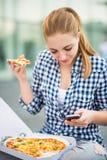 Jugendlicher, der die Pizza schaut im Telefon isst Lizenzfreies Stockfoto