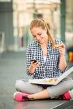 Jugendlicher, der die Pizza schaut im Telefon isst Stockfoto
