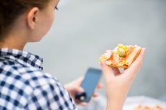 Jugendlicher, der die Pizza schaut im Telefon isst Lizenzfreie Stockfotografie