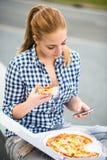 Jugendlicher, der die Pizza schaut im Telefon isst Stockfotos
