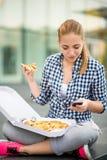 Jugendlicher, der die Pizza schaut im Telefon isst Lizenzfreies Stockbild