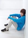 Jugendlicher, der durch die Wand sitzt Stockfotografie