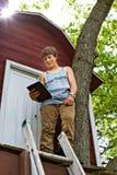 Jugendlicher, der eine Berührungsfläche liest Lizenzfreie Stockfotografie