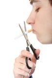 Jugendlicher, der eine Zigarette schneidet Stockfotografie