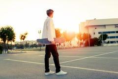 Jugendlicher, der in einen Park an einem freien Tag im sonnigen Wetter Skateboard fährt Stockbilder