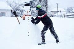 Jugendlicher, der einen Schneemann errichtet Stockfotografie