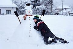 Jugendlicher, der einen Schneemann errichtet Stockfotos