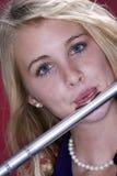 Jugendlicher in der Flöte-Leistung auf Rot lizenzfreie stockbilder