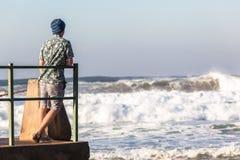 Jugendlicher, der Gezeiten- Pool-Meereswogen steht Lizenzfreie Stockfotos