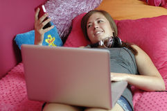 Jugendlicher, der Handy und Computer verwendet Stockbild
