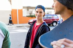 Jugendlicher, der hinunter die Straße am Sommertag geht Lizenzfreie Stockbilder