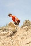 Jugendlicher, der hinunter eine Düne sandboarding ist stockbilder