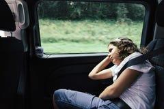 Jugendlicher, der im Rücksitze eines Autos auf einer Reise schläft lizenzfreie stockfotos