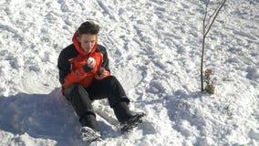 Jugendlicher, der im Schnee macht einen Schneeball und isst ihn niederlegt stock footage