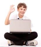 Jugendlicher, der Laptop - okaygeste verwendet Lizenzfreie Stockbilder