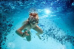 Jugendlicher in der Maske und Schnorchel schwimmen unter Wasser. lizenzfreie stockbilder
