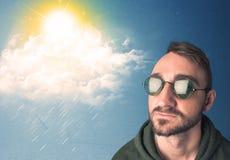 Jugendlicher, der mit Sonnenbrille Wolken und Sonne betrachtet Stockbilder
