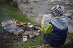 Jugendlicher, der nahe einem Feuer in kampierender und aufpassender Karte sitzt lizenzfreie stockfotografie