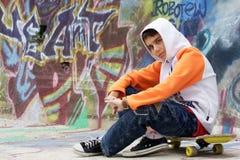 Jugendlicher, der nahe einer Graffitiwand sitzt Lizenzfreies Stockbild