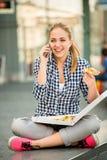 Jugendlicher, der Pizza isst und Telefon nennt Lizenzfreie Stockfotografie