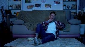 Jugendlicher, der Popcorn isst und Kan?le im Fernsehen, Zeit vergeudend, Langeweile schaltet lizenzfreie stockfotos