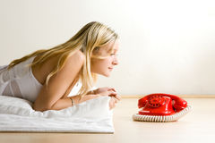 Jugendlicher, der rotes Telefon betrachtet Lizenzfreies Stockbild
