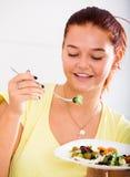 Jugendlicher, der Salat isst Lizenzfreies Stockbild