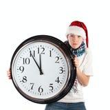 Jugendlicher in der Schutzkappe von Weihnachtsmann und von großer Borduhr Stockfotografie