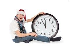Jugendlicher in der Schutzkappe von Weihnachtsmann und von großer Borduhr Stockbild