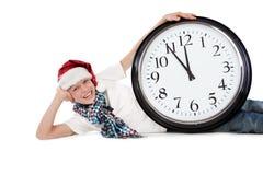 Jugendlicher in der Schutzkappe von Weihnachtsmann und von großer Borduhr Stockbilder