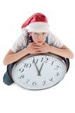 Jugendlicher in der Schutzkappe von Weihnachtsmann und von großer Borduhr Lizenzfreie Stockfotos