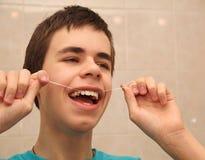 Jugendlicher mit Zahnseide Stockfotos