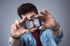 Jugendlicher, der selfies mit seinem Smartphone nimmt Lizenzfreie Stockfotos