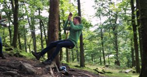 Jugendlicher, der Spaß auf einem Seil-Schwingen hat