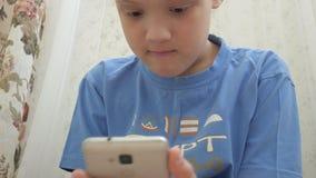 Jugendlicher, der Spiele auf Smartphone mit Aufregung beim auf Boden zu Hause sitzen spielt stock footage