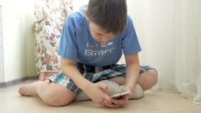 Jugendlicher, der Spiele auf Smartphone mit Aufregung beim auf Boden zu Hause sitzen spielt stock video footage