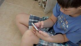 Jugendlicher, der Spiele auf Smartphone mit Aufregung beim auf Boden zu Hause sitzen spielt stock video