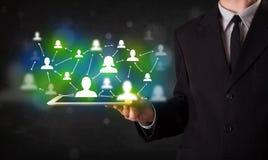Jugendlicher, der Tablette mit grünen Social Media-Ikonen darstellt Stockfoto