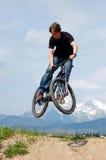 Jugendlicher, der Tricks auf Fahrrad bildet stockfotografie