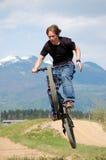 Jugendlicher, der Tricks auf Fahrrad bildet lizenzfreie stockfotos