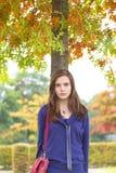 Jugendlicher, der unter einem Herbstbaum steht Stockfoto
