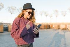 Jugendlicher des jungen Mädchens im Hut und in Gläsern, die im Handy schauen und Zeigefinger herauf Aufmerksamkeit, Idee, Eureka, lizenzfreie stockfotos