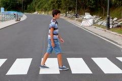 Jugendlicher durch einen Zebrastreifen Stockbilder